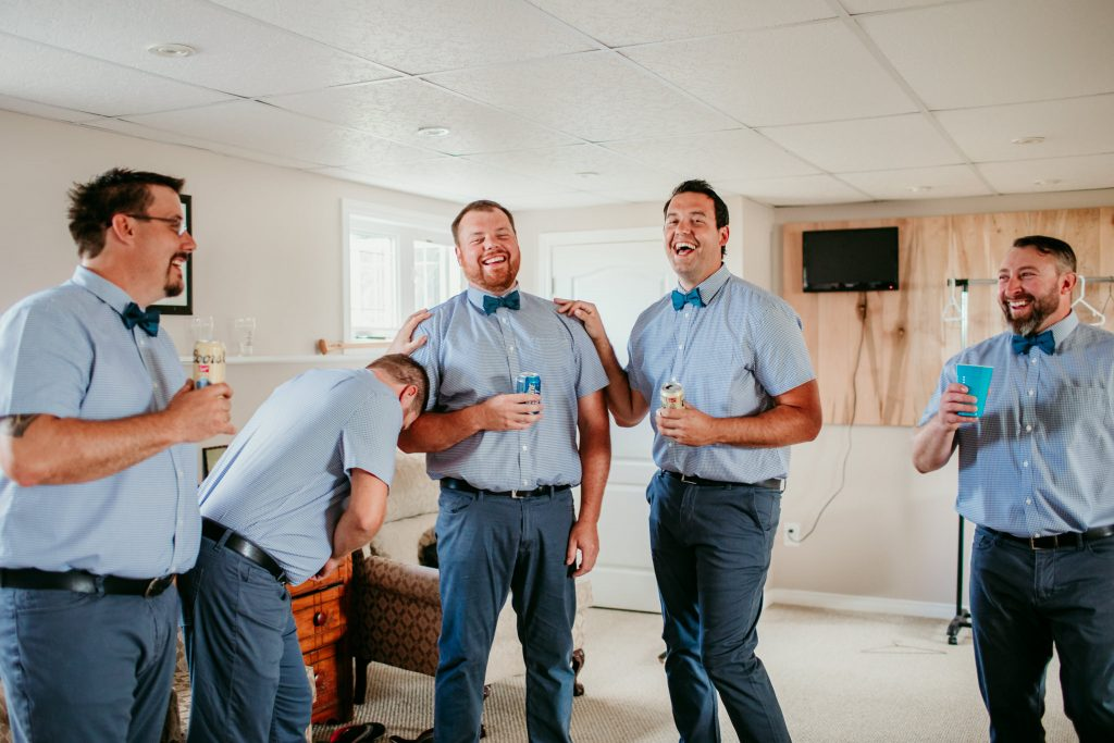 groomsmen laughing hysterically with groom