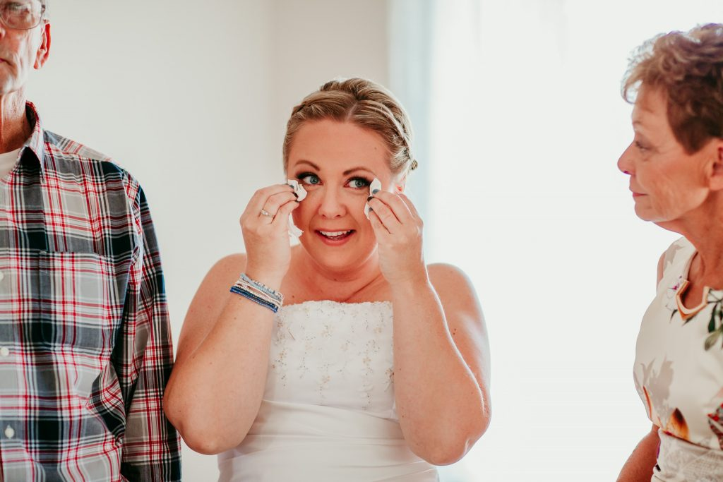 bride holding kleenex on either side of her eyes after crying while smiling