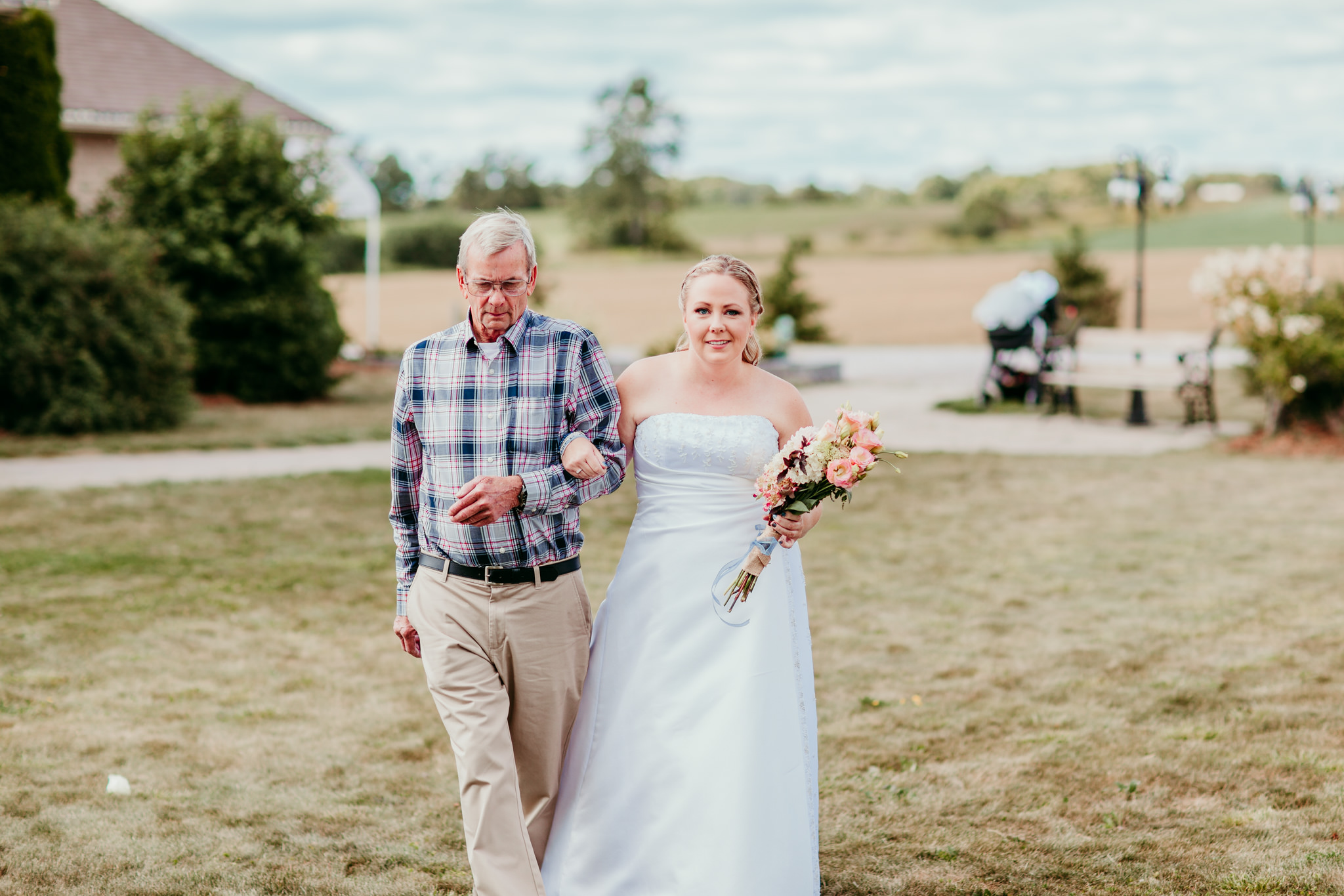bride walking down aisle with her father smiling
