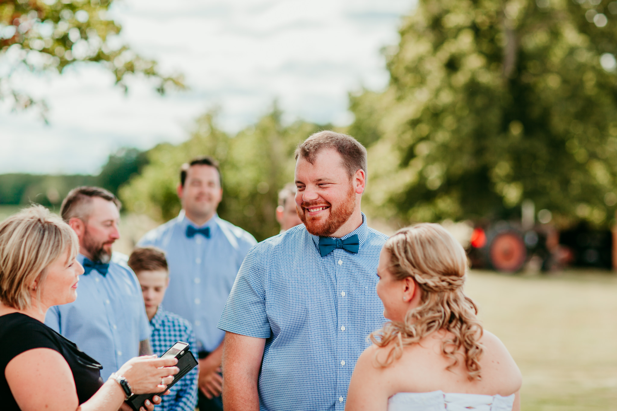 groom smiling at officiant during wedding vows