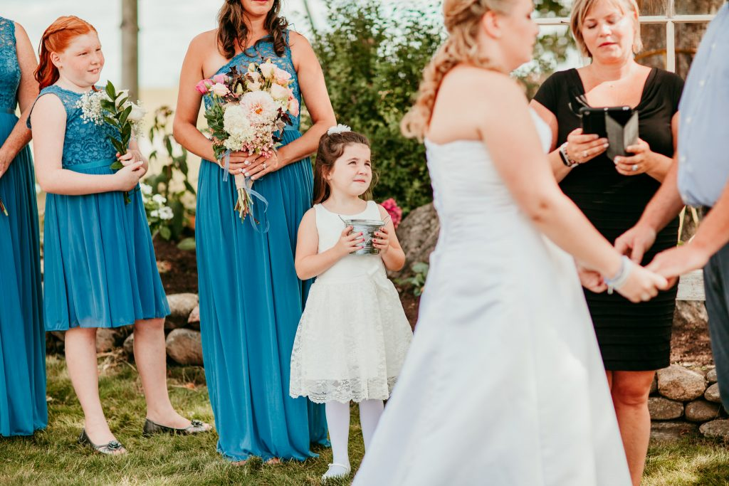 flower girl looking up at bride and groom concentrating during ceremony