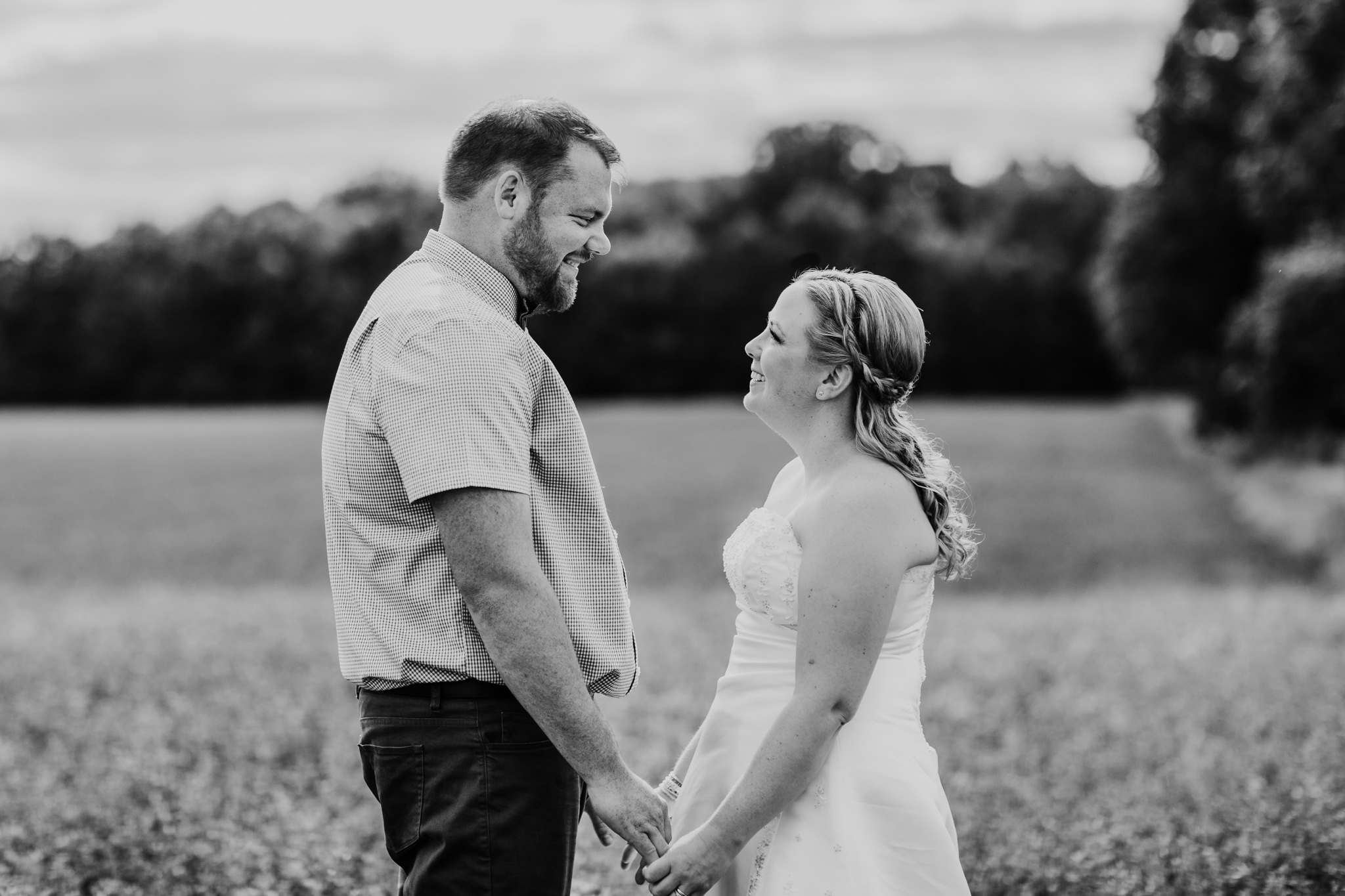 bride and groom holding hands facing each other in black and white image