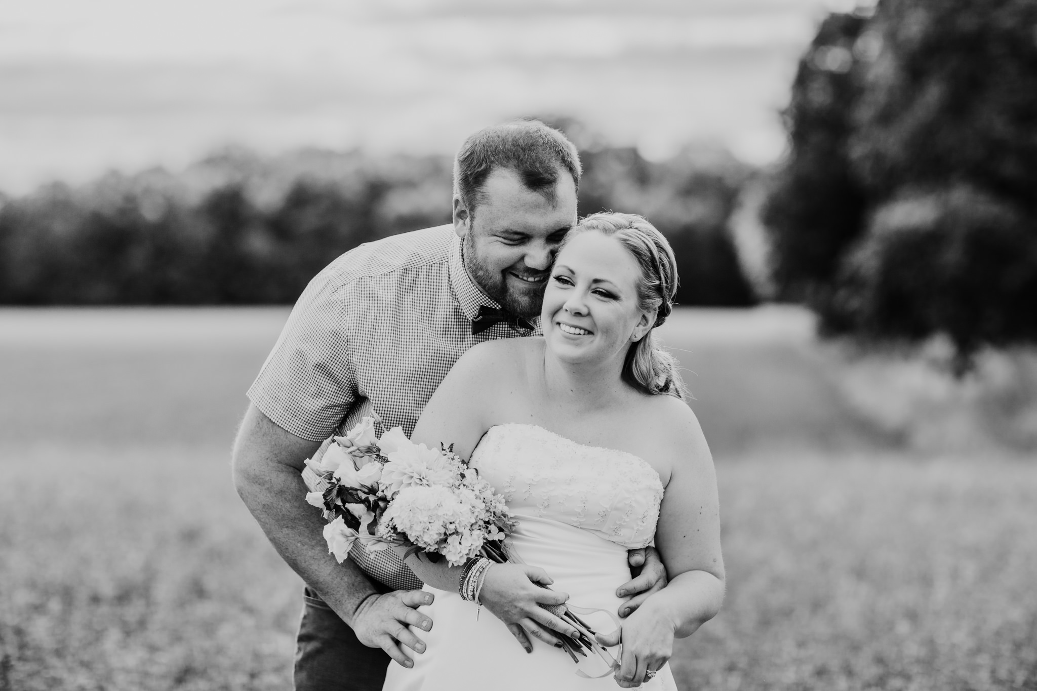 groom whispering something funny into brides ear while standing in a field