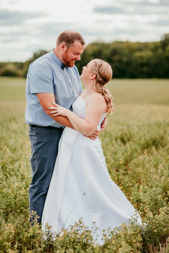 bride and groom cuddling while looking into each others eyes during wedding pictures