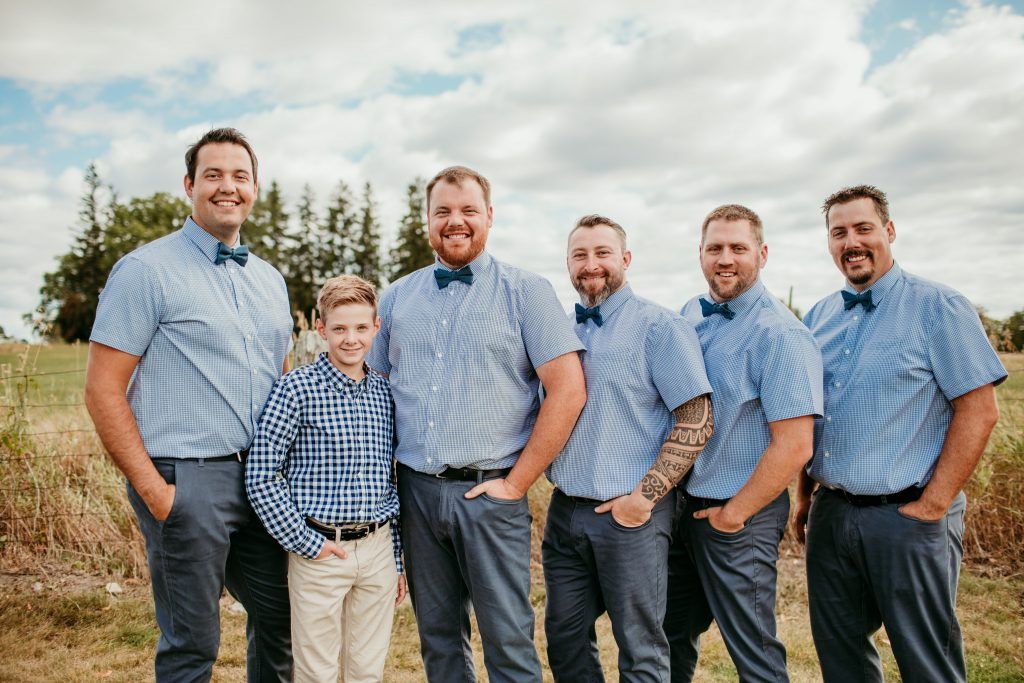 groomsmen standing smiling at the camera in blue short sleeve shirts