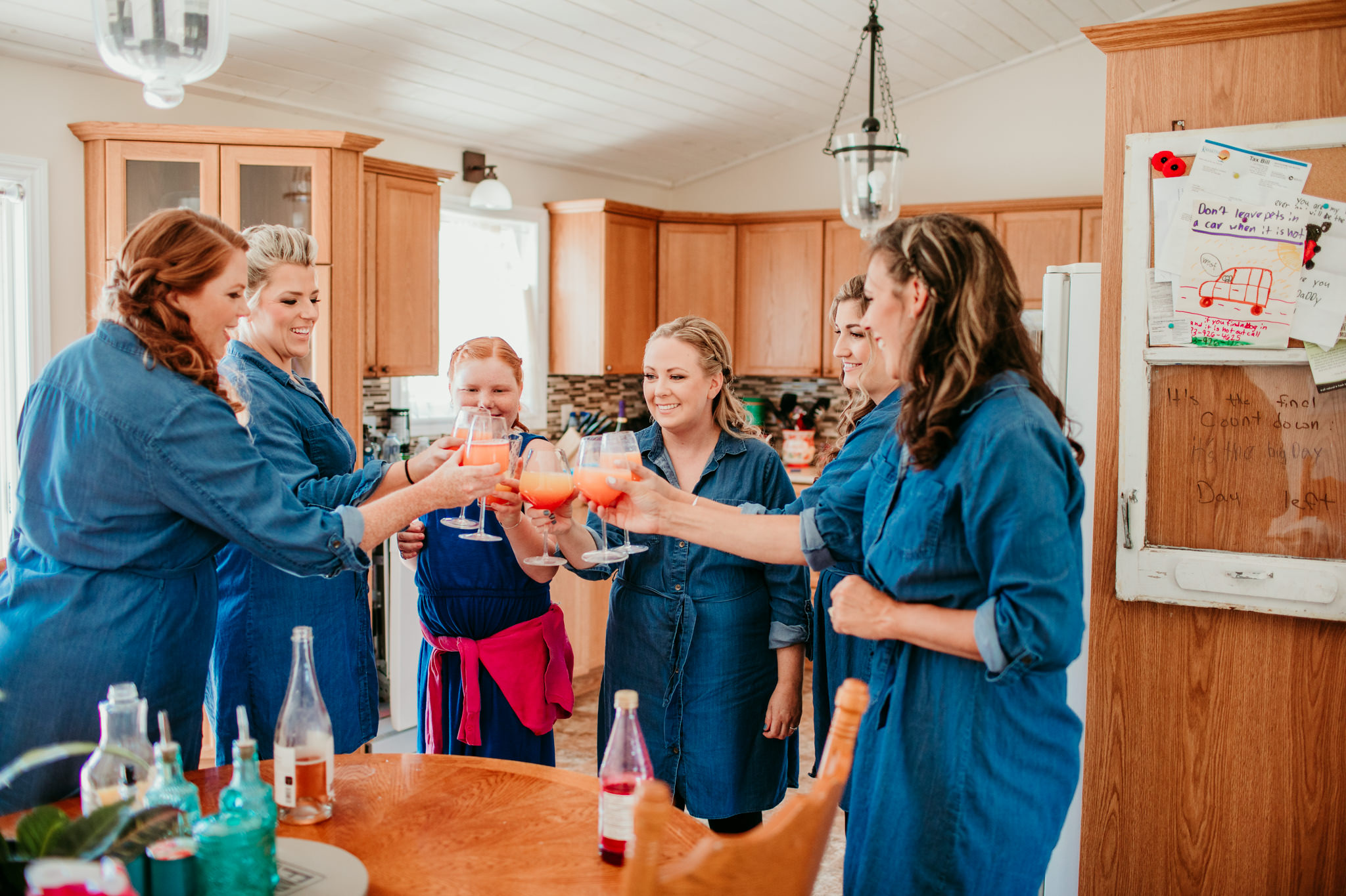 bridesmaids standing with bride doing a cheers before their wedding day
