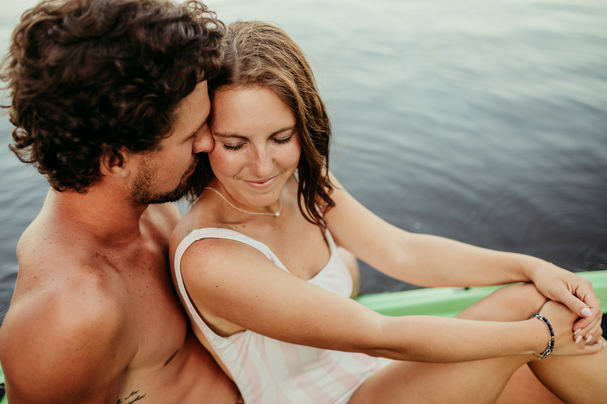 guy snuggling with his girlfriend on their lake engagement session