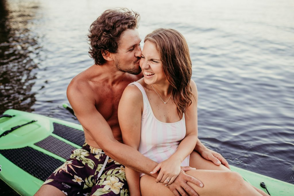 guy kissing his girlfriend on the cheek while sitting on the paddle board in the lake