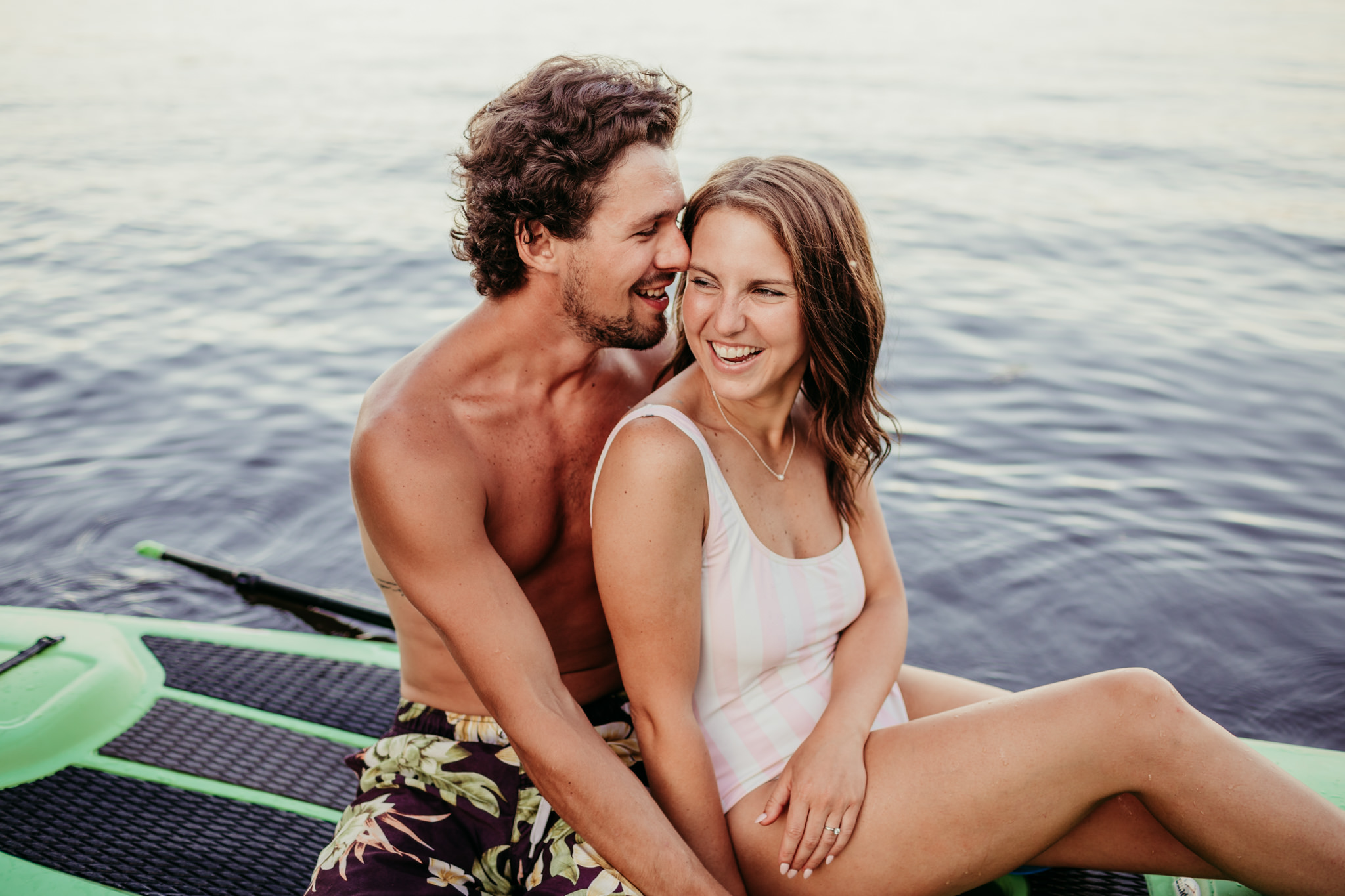 guy whispering into ear of his fiance on a lake