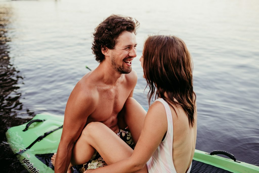 guy smiling at his girlfriend while outdoors on the lake