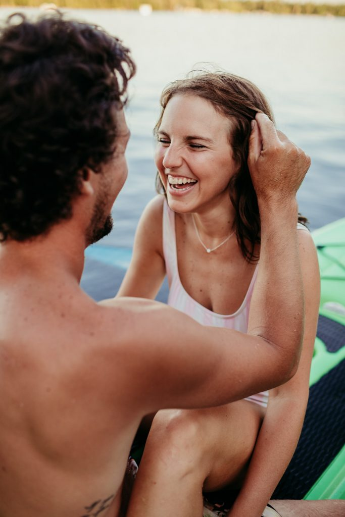 girl sitting in pink striped bathing suit laughing while boyfriend touches her hair