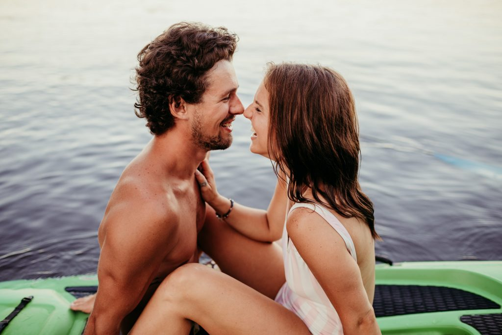 guy and girl facing each other laughing nose to nose during lakeside engagement session